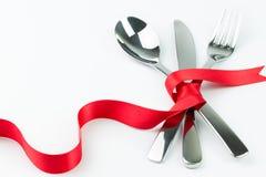 Το δίκρανο, το κουτάλι και το μαχαίρι εταιρίαξαν με την κόκκινη κορδέλλα Στοκ Εικόνες