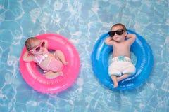 Το δίδυμα αγόρι και το κορίτσι μωρών που επιπλέουν επάνω κολυμπούν τα δαχτυλίδια στοκ φωτογραφίες
