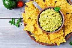 Το αβοκάντο, ο ασβέστης, η ντομάτα, το κρεμμύδι και το cilantro Guacamole, εξυπηρέτησαν με τα nachos Στοκ Εικόνες