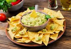 Το αβοκάντο, ο ασβέστης, η ντομάτα, το κρεμμύδι και το cilantro Guacamole, εξυπηρέτησαν με τα nachos Στοκ φωτογραφία με δικαίωμα ελεύθερης χρήσης