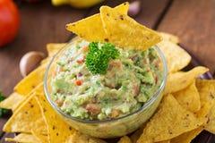 Το αβοκάντο, ο ασβέστης, η ντομάτα, το κρεμμύδι και το cilantro Guacamole, εξυπηρέτησαν με τα nachos στοκ φωτογραφίες