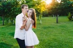 Το αγαπώντας άτομο αγκαλιάζει το κορίτσι του σε μια πράσινη περιοχή στοκ φωτογραφία