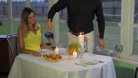 Το αγαπώντας ζεύγος το βράδυ για ένα ρομαντικό γεύμα, άνδρας χύνει στη γυναίκα το κόκκινο κρασί απόθεμα βίντεο