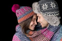 Το αγαπώντας ζεύγος στα θερμά ενδύματα αγκαλιάζει απομονωμένος στο μαύρο υπόβαθρο Στοκ φωτογραφία με δικαίωμα ελεύθερης χρήσης