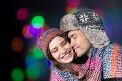 Το αγαπώντας ζεύγος στα θερμά ενδύματα αγκαλιάζει στο μαύρο υπόβαθρο Στοκ εικόνες με δικαίωμα ελεύθερης χρήσης