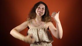 Το αγαπώ γυναίκα που κάνει όπως το α όπως με τους αντίχειρες επάνω σε ένα πορτοκαλί υπόβαθρο φιλμ μικρού μήκους