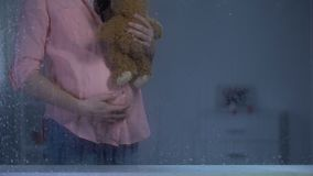 Το αγκάλιασμα εγκύων γυναικών teddy αντέχει πίσω από το βροχερό παράθυρο, προσδοκία μωρών, προσοχή απόθεμα βίντεο