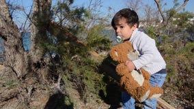 Το αγκάλιασμα μικρών παιδιών teddy αντέχουν και η αναρρίχηση στον περίπατο δέντρων thann προς τη κάμερα φιλμ μικρού μήκους