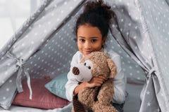 το αγκάλιασμα παιδιών αφροαμερικάνων teddy αντέχουν και το κοίταγμα Στοκ εικόνα με δικαίωμα ελεύθερης χρήσης