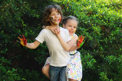 Το αγκάλιασμα παιδάκι, τα πρόσωπα και τα χέρια τους είναι χρωματισμένα Στοκ Φωτογραφία