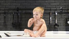 Το αγοράκι δοκιμάζει τη ζάχαρη όταν δεν τον βλέπει κανένα Το γυμνό χαριτωμένο νήπιο κάθεται στον πίνακα κουζινών 4K απόθεμα βίντεο