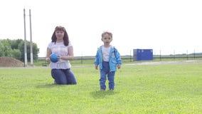 Το αγοράκι και η μητέρα του παίζουν με μια σφαίρα στην πράσινη χλόη φιλμ μικρού μήκους