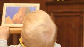 9-10 το αγοράκι μηνών εξετάζει τη νεογέννητη φωτογραφία του απόθεμα βίντεο