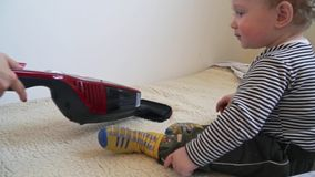 Το αγοράκι παίζει με την ηλεκτρική σκούπα έως ότου σκουπίζει με ηλεκτρική σκούπα η μητέρα απόθεμα βίντεο