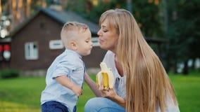 Το αγοράκι φιλά το mom του Στηρίζονται στο προαύλιο του σπιτιού τους, το αγόρι έφαγε μια μπανάνα απόθεμα βίντεο
