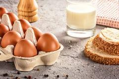 Το αγροτικό ακατέργαστο φρέσκο αυγό στο γάλα ψωμιού πακέτων στον γκρίζο πίνακα ανακάτωσε το τηγανισμένο ομελέτα αυγό αυγών Στοκ φωτογραφία με δικαίωμα ελεύθερης χρήσης
