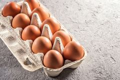 Το αγροτικό ακατέργαστο φρέσκο αυγό στο πακέτο στον γκρίζο πίνακα ανακάτωσε το τηγανισμένο ομελέτα αυγό αυγών Στοκ Εικόνα
