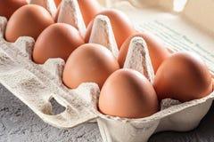 Το αγροτικό ακατέργαστο φρέσκο αυγό στο πακέτο στον γκρίζο πίνακα ανακάτωσε το τηγανισμένο ομελέτα αυγό αυγών Στοκ εικόνες με δικαίωμα ελεύθερης χρήσης