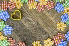 Το αγροτικό ξύλινο υπόβαθρο με την κίτρινη καρδιά, ύφασμα ανθίζει scatt Στοκ εικόνα με δικαίωμα ελεύθερης χρήσης