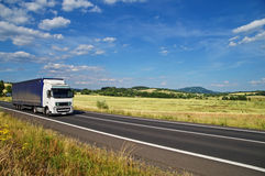 Το αγροτικό τοπίο με το δρόμο εσείς οδηγεί ένα άσπρο φορτηγό στοκ φωτογραφίες