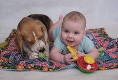 Το λαγωνικό και το μωρό που βρίσκονται στο χαλί Στοκ φωτογραφία με δικαίωμα ελεύθερης χρήσης