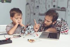 Το αγόρι έβλαψε το ρομπότ Ένα άτομο τιμωρεί σοβαρά το αγόρι, που εξηγεί σε τον τα λάθη του Στοκ εικόνα με δικαίωμα ελεύθερης χρήσης