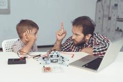 Το αγόρι έβλαψε το ρομπότ Ένα άτομο τιμωρεί σοβαρά το αγόρι, που εξηγεί σε τον τα λάθη του Στοκ εικόνες με δικαίωμα ελεύθερης χρήσης