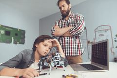 Το αγόρι έβλαψε το ρομπότ Ένα άτομο τιμωρεί σοβαρά το αγόρι, που εξηγεί σε τον τα λάθη του Στοκ Φωτογραφία