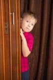Το αγόρι έκρυψε πίσω από την ντουλάπα Στοκ εικόνες με δικαίωμα ελεύθερης χρήσης