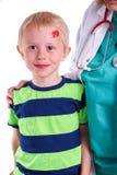 Το αγόρι έχει τον τραυματισμό στο μέτωπο και παίρνει τη βοήθεια από το γιατρό Στοκ φωτογραφία με δικαίωμα ελεύθερης χρήσης