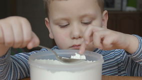 Το αγόρι αγγίζει το αλεύρι και τα χαμόγελα και τον αντίχειρα επάνω απόθεμα βίντεο