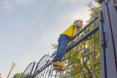 Το αγόρι αναρριχήθηκε επάνω στο φράκτη Το παιδί αναρριχείται στην πύλη, Φε στοκ φωτογραφία με δικαίωμα ελεύθερης χρήσης