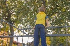 Το αγόρι αναρριχήθηκε επάνω στο φράκτη Το παιδί αναρριχείται στην πύλη, Φε στοκ φωτογραφία
