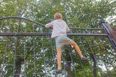 Το αγόρι αναρριχήθηκε επάνω στο φράκτη Το παιδί αναρριχείται στην πύλη, Φε στοκ εικόνες