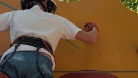 Το αγόρι αναρριχείται στη σειρά μαθημάτων εμποδίων στο στρατόπεδο Ένα γενναίο αγόρι εκπληρώνει τα πρότυπα ανιχνεύσεων αγοριών απόθεμα βίντεο