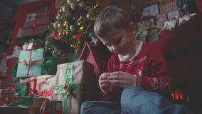 Το αγόρι ανοίγει ένα κιβώτιο με ένα χριστουγεννιάτικο δώρο και το παίρνει απόθεμα βίντεο
