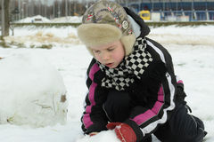 Το αγόρι απασχολείται επιμελώς sculpts σε έναν χιονάνθρωπο στοκ εικόνες