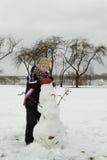 Το αγόρι απασχολείται επιμελώς sculpts σε έναν χιονάνθρωπο στοκ φωτογραφίες