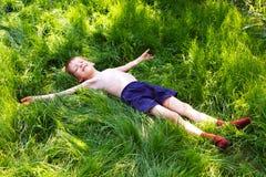 Το αγόρι βάζει σε μια πράσινη χλόη. Στοκ φωτογραφία με δικαίωμα ελεύθερης χρήσης
