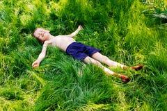 Το αγόρι βάζει σε μια πράσινη χλόη. Στοκ φωτογραφίες με δικαίωμα ελεύθερης χρήσης