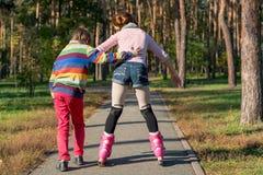 Το αγόρι βοηθά το κύλινδρος-σαλάχι κοριτσιών στο πάρκο Αδελφός supp στοκ εικόνα