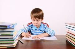 Το αγόρι γράφει στο βιβλίο άσκησης Στοκ Φωτογραφία