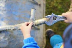 Το αγόρι δίνει τη βίδα βιδώματος με το γαλλικό κλειδί Στοκ εικόνες με δικαίωμα ελεύθερης χρήσης