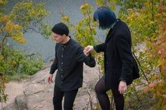 Το αγόρι δίνει το χέρι για το μπλε κορίτσι τρίχας στο βράχο στην ακτή Στοκ Εικόνες