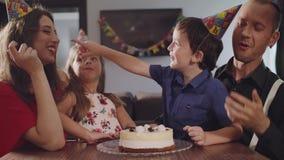 Το αγόρι δαγκώνει ένα κέικ γενεθλίων απόθεμα βίντεο