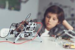 Το αγόρι δημιουργεί ένα ρομπότ Μετρά τα στοιχεία του με ένα πολύμετρο Το αγόρι παρατηρεί τις μετρήσεις Στοκ φωτογραφίες με δικαίωμα ελεύθερης χρήσης