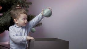 Το αγόρι διακοσμεί ένα χριστουγεννιάτικο δέντρο απόθεμα βίντεο