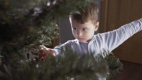 Το αγόρι διακοσμεί ένα χριστουγεννιάτικο δέντρο φιλμ μικρού μήκους