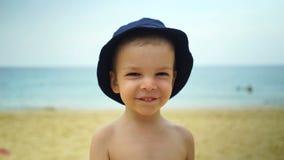 Το αγόρι δύο ετών στέλνει ένα φιλί αέρα στην παραλία κοντά στον ωκεανό απόθεμα βίντεο