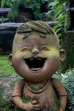 Το αγόρι είναι άγαλμα γέλιου στον κήπο λουλουδιών στοκ φωτογραφίες